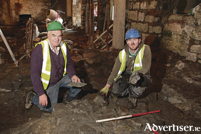 Building contractor Sean Duane of Duane Construction, and archaeologist David Kelly with the recently uncovered 13th century castle walls at Quay Street. 