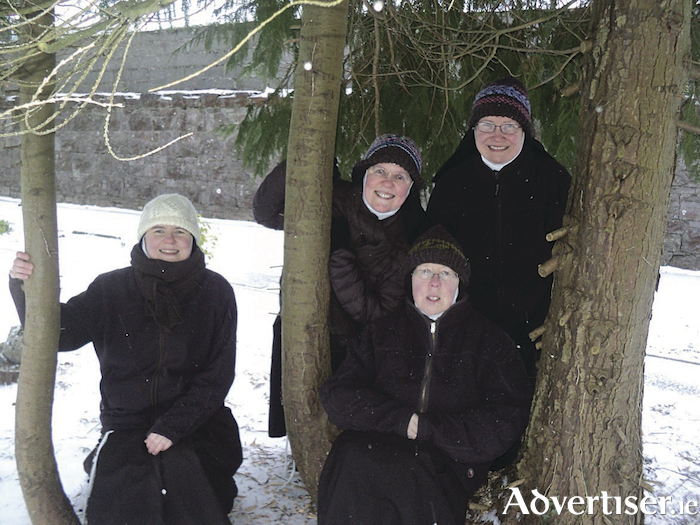 Sisters sheltering from the snow under the the trees.