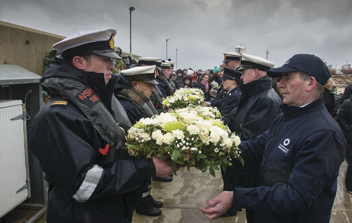 Wreaths to be laid in the sea near the crash site of R116 are handed over to members of the Irish Naval Service, by members of emergency services in Blacksod on Wednesday. Photo: Michael McLaughlin.