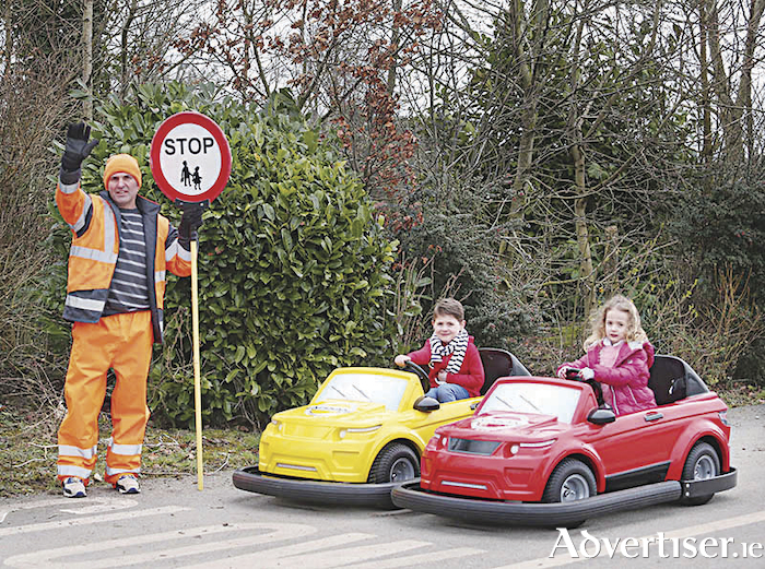 Local lollipop man David Mitchell from St Andrew's National School, Asbourne, Co Meath, with twins Conor and Tara Ocks aged four who are the first children to try out the cars that will be driven at the Nissan Driving School at Tayto Park.  Photo: Leon Farrell/Photocall Ireland.