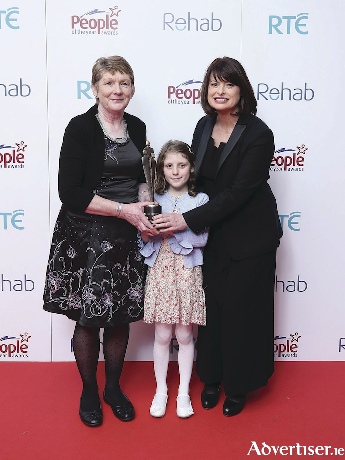 Human Rights Commissioner Emily Logan (right) presents Catherine Corless with a People of the Year Award, alongside her grand-daughter Aoife Moriarty.