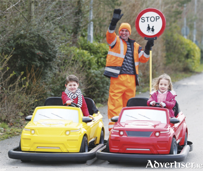 Lollipop man David Mitchell with Twins Conor and Tara Ocks, aged four, who were the first children to try out the cars that will be driven at the Nissan Driving School at Tayto Park. Photo: Leon Farrell/Photocall Ireland