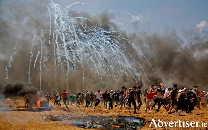 Palestinians flee from tear gas fired by Israeli soldiers during the protests in Gaza.
