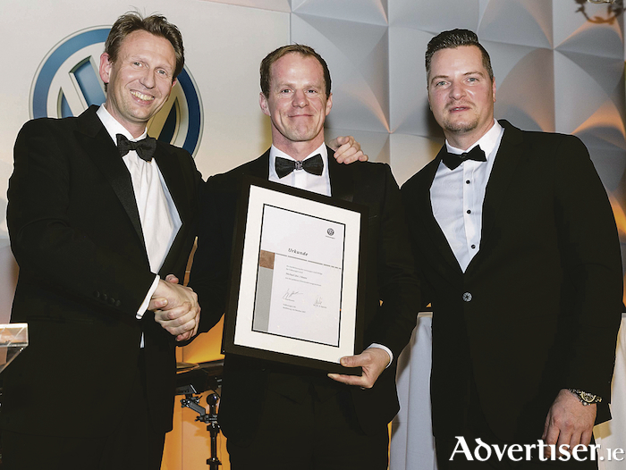 Michael Moore Junior (centre) picking up the Gold Pin Award from Volkswagen Ireland brand director, Gerrit Heimberg (on the left), and Joerg Hertwig, area sales manager for Northwest Europe (on the right) at an awards ceremony in Kildare