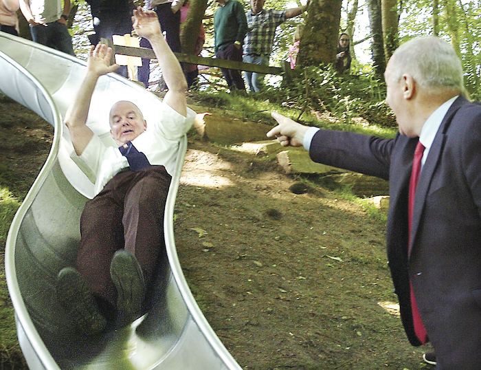 Hands across party lines: Minister Michal Ring gives some encouragement to Cllr Blackie Gavin - as he tried out the slide at the new Turlough community playground. Photo: Henry Wills