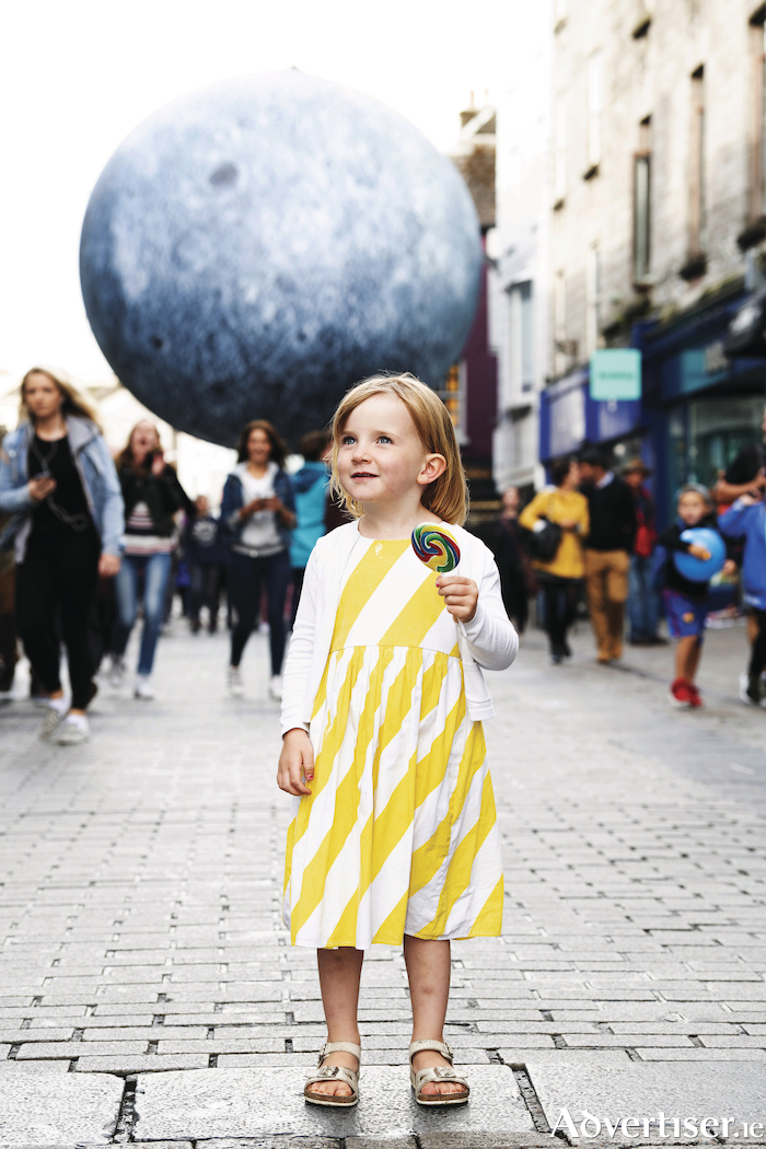It's behind you! Four-year-old Esme O'Connor from Hollymount enjoying the Luke Jerram's Museum of the Moon, measuring seven metres in diameter and featuring 120dpi detailed NASA imagery of the lunar surface, pictured in Shop Street, Galway, as part of Galway International Arts Festival. Photo: Andrew Downes, Xposure.