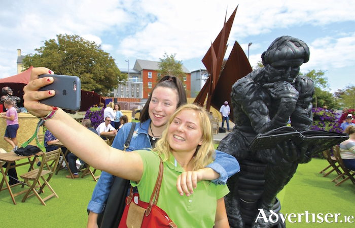 Laura Flynn (Lackagh) Anna Conneely (Athenry) pose beside a statue at the GIAF 18 Festival Garden in Eyre Square. Photo:- Mike Shaughnessy