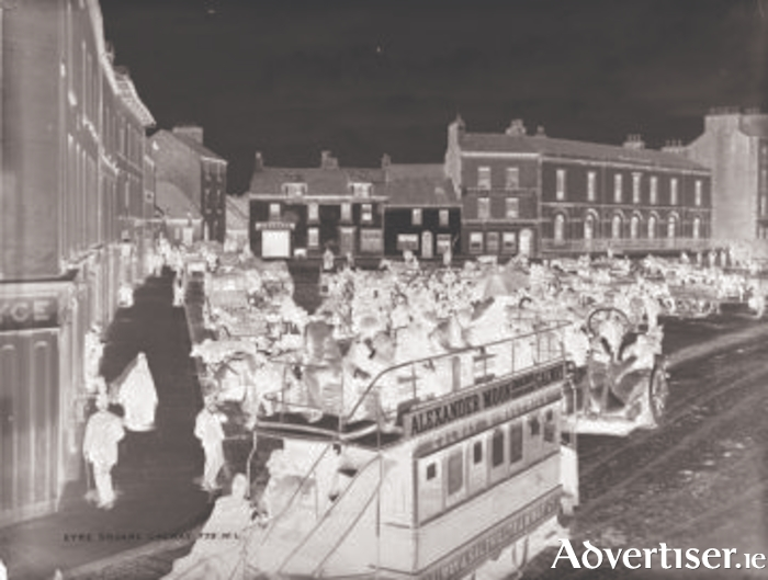 A crowded double-decked tram leaving Eyre Square  heading to Salthill. Note the double track lines to allow a second tram pass in the opposite direction.
