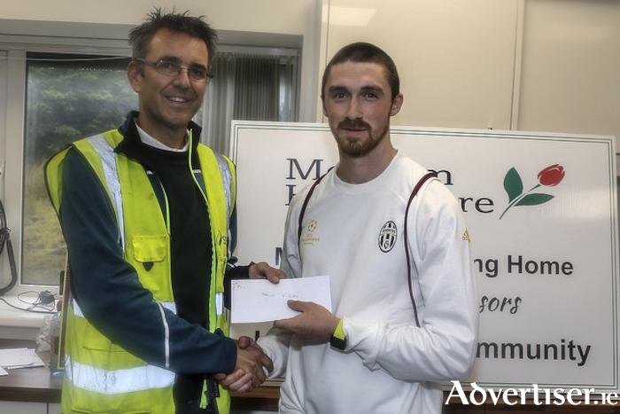 Naoise O Gibne of GCH, winner of the Corrib AC 8km, receives first prize from John O'Sullivan of the Galway Wind Park.              Photo: John O'Connor