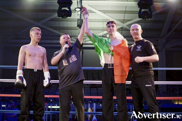 Galway Black Dragon Kickboxer Alex Fitzpatrick from Tuam has his hand raised by referee Pete Richardson at the  Planet Ice arena in Milton Keynes on Saturday night after he knocked out his opponent from Cyprus with a head kick in the 38th second of the first round. Fitzpatrick is pictured here with a dleighted coach Pete Foley.