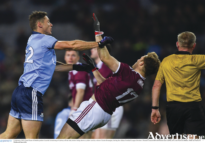 Paul Flynn of Dublin pushes Sean Armstrong of Galway off the ball, before being shown a yellow card by referee Ciaran Branagan, during the Allianz Football League division one match between Dublin and Galway at Croke Park in Dublin.			 Photo:	Piaras  Macdheach/Sportsfile
