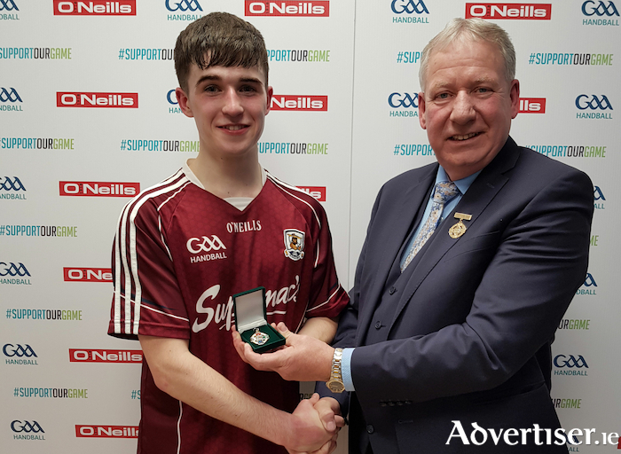 Moycullen's Diarmuid Mulkerrins, winner of the All-Ireland U21 40x20 Handball title receives his medal from Joe Masterson, GAA Handball president.