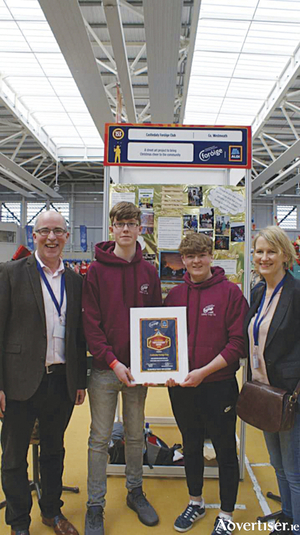 Martin Donohue of Foróige and Linda O'Sullivan of DCYA present Jay Loolney and Cathal Fitzmaurice from Castledaly Foróige Club with a certificate of achievement at the Aldi Foróige Youth Citizenship awards.