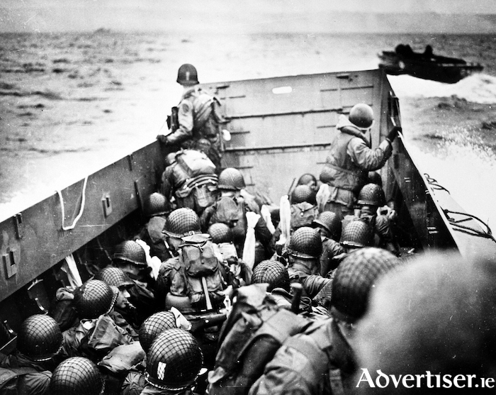 American assault troops in a landing craft huddle behind the shield on June 6, 1944