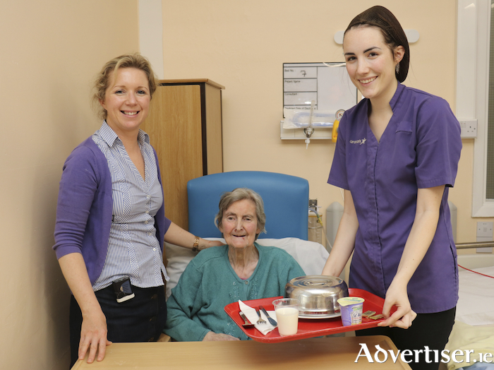 From left: June Barrett, senior dietitian, patient Sheila Rabbitte, and catering staff member Aoife Fahy, with a red tray to illustrate the new initiative at University Hospital Galway.