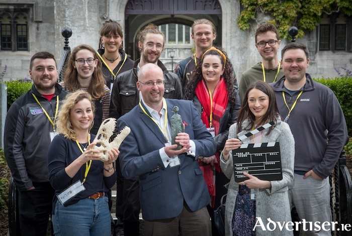 Dr John Murray (centre, holding MEDEA Award statuette) and some previous History of Life student film-makers celebrate this year's win at the 2019 MEDEA Awards in Belgium.  Front row L-R: Orla Bath-Enright (2014, holding dinosaur skull), Alida Zauers (2015, holding clapperboard). Middle row L-R: Shane McQuillan (2019), Rebecca O'Connor (2015), Oscar Ryan (2018), Eavan Collins (2014), Weston Harding (2019). Back Row L-R: Bébhinn Anders (2015), James Burns (2019), Seán Wheeler (2014). 