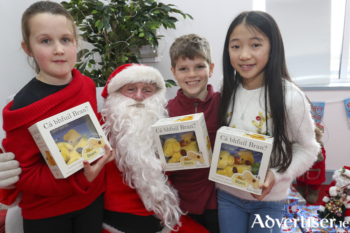 Iseult Ní Ghibne, Cuan Canny, and Sara Ní Choinceanainn happily show off their  'Bran' presentation box with toy and book from An Gúm publisher during their visit to Santa at Cló Iar-Chonnacht's bookshop in An Spidéal, Co Galway. The event was organised by publishers Cló Iar-Chonnacht and Love Leabhar Gaeilge to promote Irish-language children's books. Pic: Seán Ó Mainnín