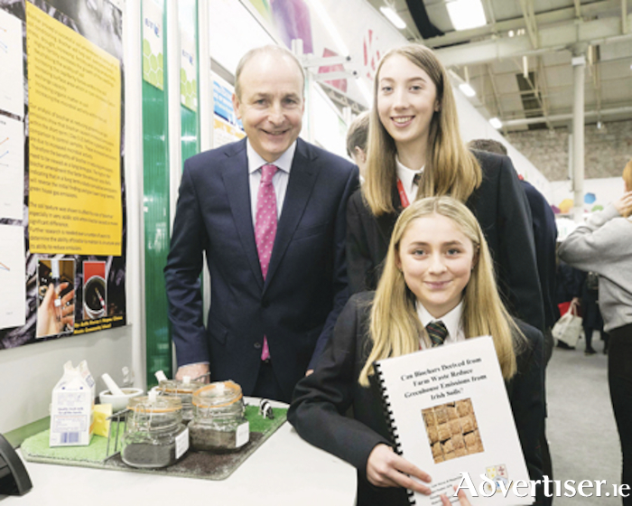 Michael Martin, TD meets Aoife Murray and Megan Clinton from Moate Community School Westmeath with their project 'Can Biochars derived from farm waste reduce greenhouse emmissions from Irish soils?' at the BT Young Scientist & Technology Exhibition in the RDS Dublin. 