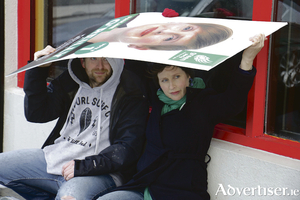 Sudden climate change - Green Party candidate Pauline O'Reilly and her helper Brian McGrady take shelter from a hail shower under one of her election posters in the city yesterday (Wednesday). Photo:-Mike Shaughnessy