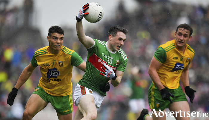 Holding on: Patrick Durcan tries to hold onto the ball under pressure from Odhran McFadden Ferry in the Super 8 meeting between Mayo and Donegal last August. Photo: Sportsfile