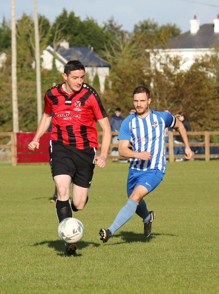 On the ball: Joe Lawless looks to get the ball away despite the pressure of Benny Lavelle. Photo: Ballina Town Facebook
