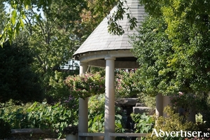A roofed gazebo makes a lovely focal point surrounded by pretty planting.