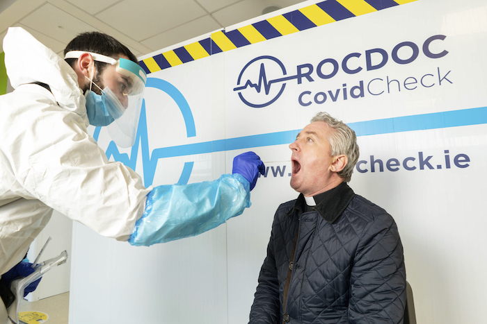 Open wide: Darragh McMahon, RocDoc swabbing staff, performing a Covid-19 swab test on Fr Richard Gibbons PP, Knock, at the new RocDoc Covid-19 testing centre in Ireland West Airport Knock, Co Mayo. Photo : Keith Heneghan.